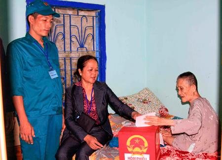 Tổ bầu cử mang thùng phiếu đến tận nhà để bà Đào Thị Này (ở đảo Trí Nguyên, phường Vĩnh Nguyên, TP. Nha Trang) bỏ phiếu bầu. Ảnh: M.H