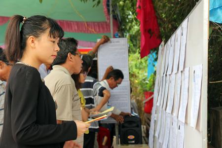 Nhiều cử tri đọc lại tiểu sử các ứng cử viên trước khi bỏ phiếu.